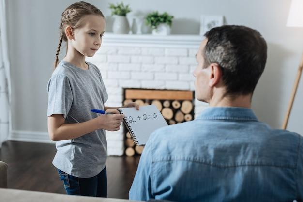 노트북을 들고 그녀의 아빠 근처에 서서 수학에 대한 그의 도움을 요청하는 꽤 사랑스러운 fair-haired 어린 소녀