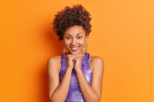 Симпатичная модная женщина с кудрявыми волосами держит руки под улыбкой подбородка, позитивно одетая в стильную одежду, выражает положительные эмоции, изолированные на ярко-оранжевой стене