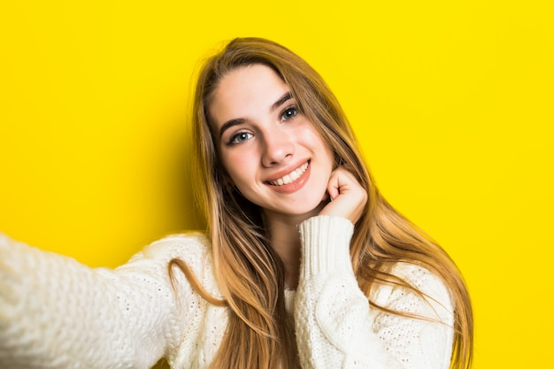 Pretty lovely smiling fashioned girl is making selfie on her phone wearing wide white sweater on yellow