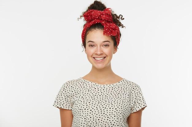 Bella donna graziosa con i capelli ricci castani raccolti in una crocchia sorride piacevolmente, vestita con una maglietta bianca a pois neri
