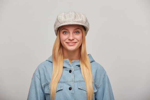 Pretty lovely young blonde woman with long hair down, looking glad, smiling, wearing oversize denim jacket and beige checked hat cap
