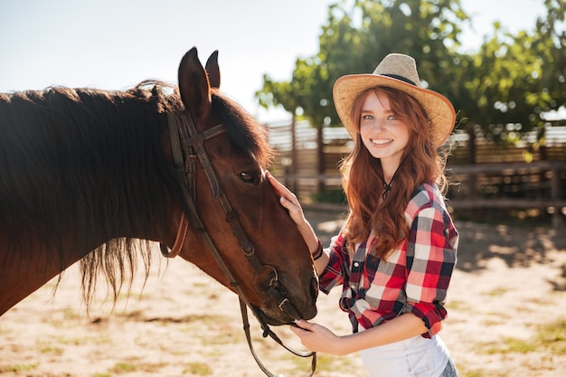 Pretty lovely young woman cowgirl taking care of her horse on ranch
