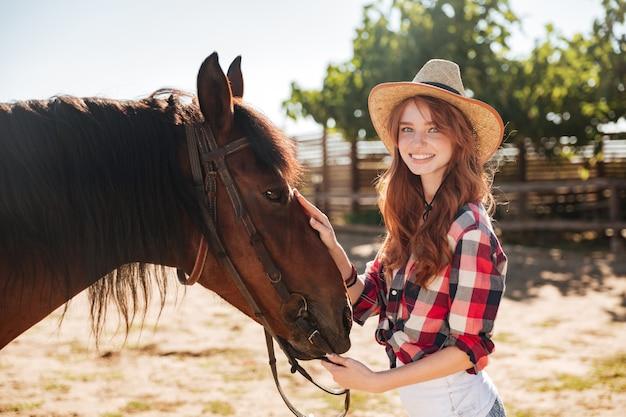 목장에서 그녀의 말을 돌보는 꽤 사랑스러운 젊은 여자 카우걸