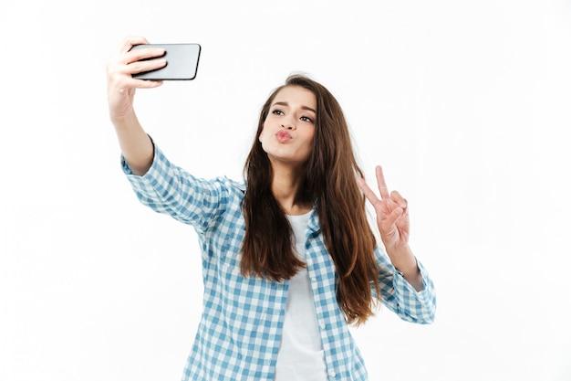 Giovane donna abbastanza adorabile che fa selfie e che mostra gesto di vittoria