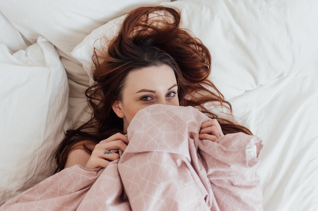 Pretty lovely young woman peeks out of bedsheets covers