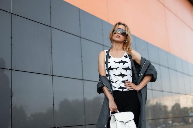 최신 유행의 옷을 입고 유행 선글라스에 꽤 럭셔리 젊은 빨간 머리 여자는 현대적인 건물 근처 도시에서 포즈. 여름 날에 산책에 미국 여자 패션 모델. 스트리트 스타일.