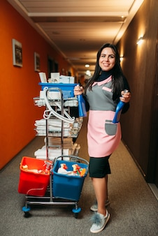 Pretty maid rolls the cart with detergents