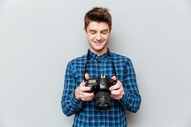Uomo grazioso che esamina le immagini la macchina fotografica