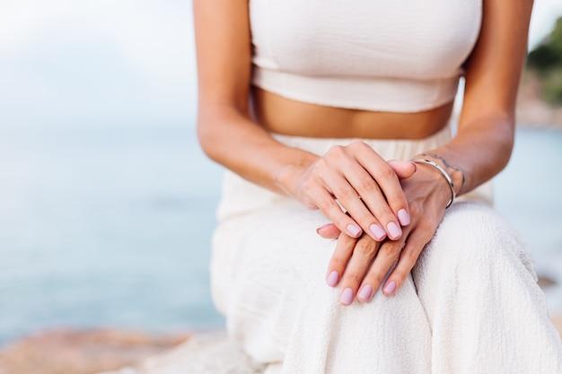 Довольно ухоженные женские руки на коленях
