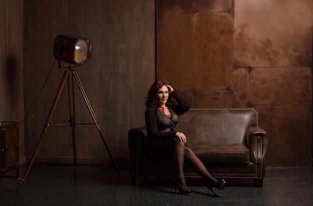 暗い部屋の革のソファでポーズをとってファッショナブルなアパレルでかなり成熟したブルネットの女性