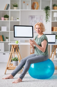 Pretty mature female with smartphone sitting on fitball while searching for online fitness course during self isolation at home