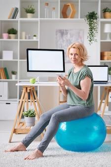自宅での自己隔離中にオンラインフィットネスコースを検索しながら、スマートフォンがフィットボールに座っているかなり成熟した女性