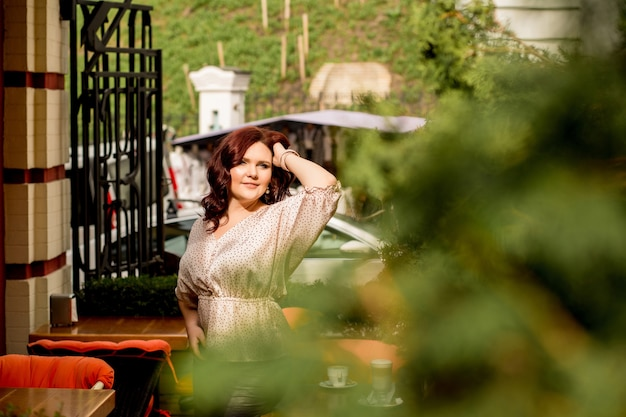 クロベの木のあるテラスでポーズをとるシルクのブラウスを着たかなり成熟した赤い髪の女性。テキスト用のスペース