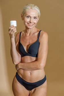 Pretty mature woman in black underwear smiling and holding white jar of cream beauty product in her