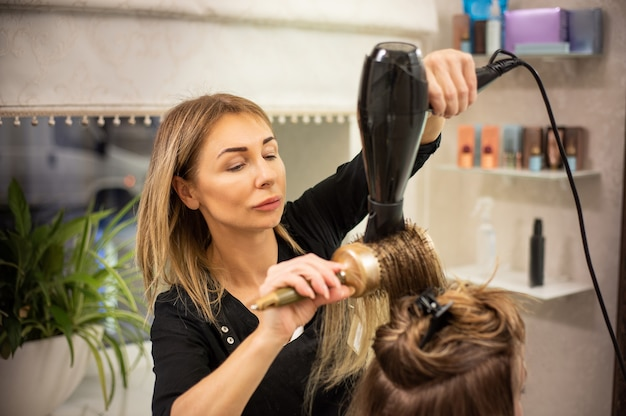 Pretty mature woman hairdresser enjoying working in beauty salon and blowdrying hair of client