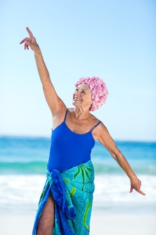 Pretty mature woman raising her arms on the beach