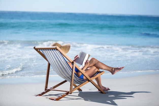 Pretty mature woman reading a book lying on deck chair