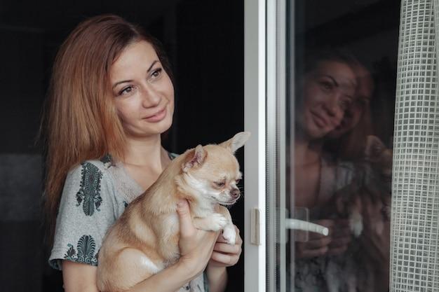 家のバルコニーで手にチワワ犬とかなり成熟した女性。中年女性と彼女の犬のチワワ。コンセプトペットの愛と家族の友人