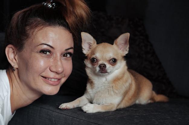 自宅のリビングルームの暗いソファにチワワ犬とかなり成熟した女性。中年女性と彼女の犬のチワワ。コンセプトペットの愛と家族の友人