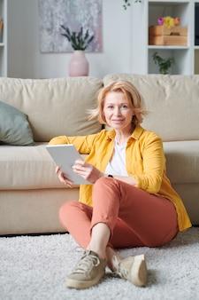 余暇または自宅の自己隔離期間中にソファで床でリラックスしたデジタルタブレットを持つかなり成熟した女性