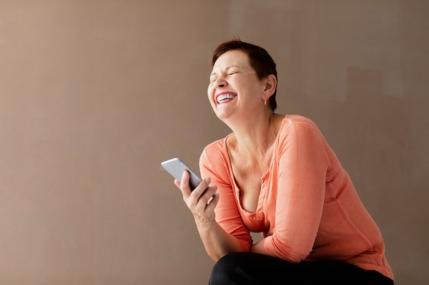 Pretty mature woman with phone laughing