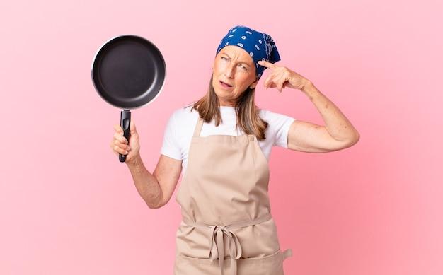 Довольно женщина среднего возраста чувствует себя смущенной и озадаченной, показывая, что вы сумасшедший, и держит сковородку. концепция шеф-повара