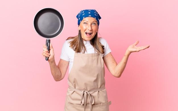 Довольно женщина среднего возраста чувствует себя счастливой и удивленной чему-то невероятным и держит сковородку. концепция шеф-повара