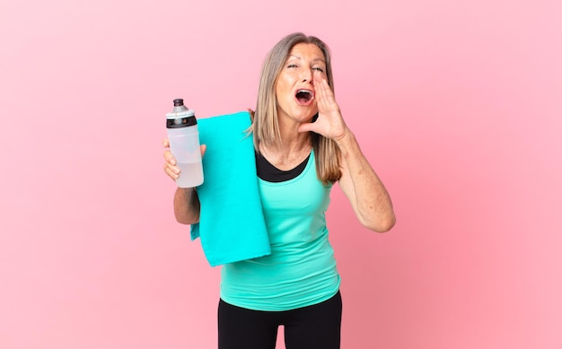 Довольно женщина среднего возраста чувствует себя счастливой, громко кричит, прижав руки ко рту. фитнес-концепция
