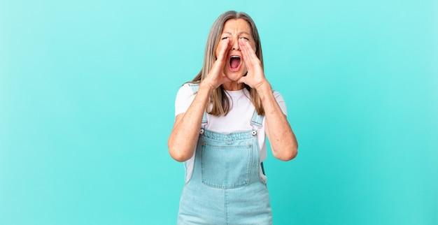 幸せを感じて、口の横に手で大きな叫び声をあげるかなり中年の女性