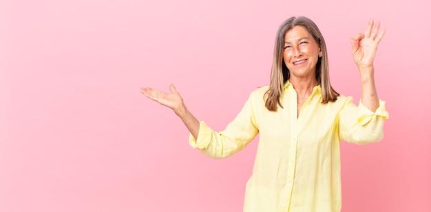 かなり中年の女性が幸せを感じ、大丈夫なジェスチャーで承認を示しています