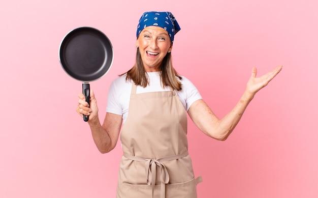 Довольно женщина среднего возраста чувствует себя счастливой, удивленной, осознавая решение или идею и держа сковороду. концепция шеф-повара