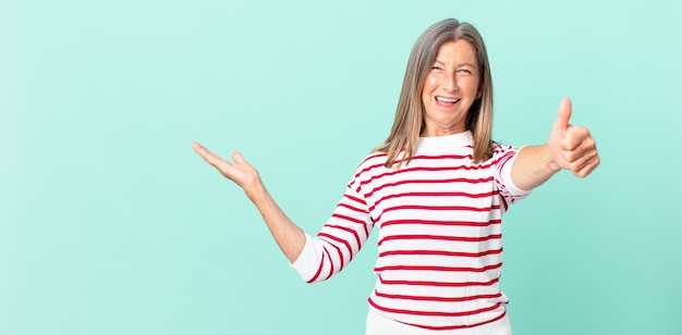 かなり中年の女性が誇りを感じ、親指を立てて前向きに笑っている