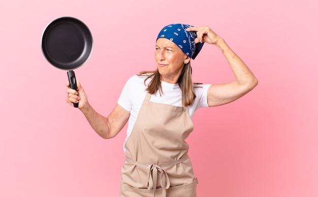 Довольно женщина среднего возраста чувствует себя озадаченной и сбитой с толку, почесывая голову и держа сковородку. концепция шеф-повара