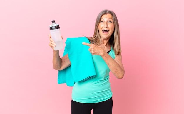 Довольно женщина среднего возраста выглядит возбужденным и удивленным, указывая в сторону. фитнес-концепция