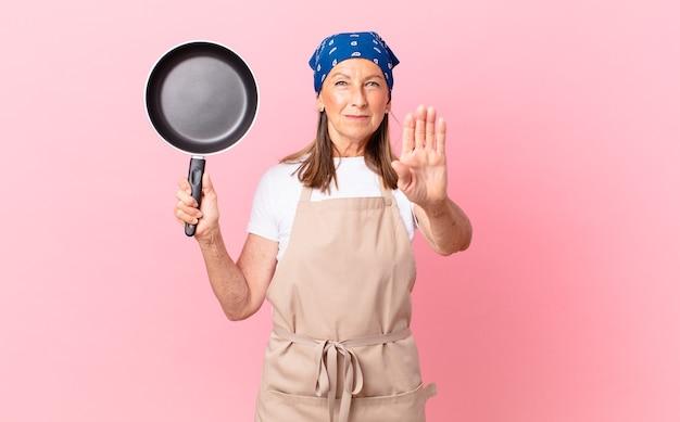Довольно женщина среднего возраста выглядит серьезным, показывая открытую ладонь, делая стоп-жест и держа сковороду. концепция шеф-повара