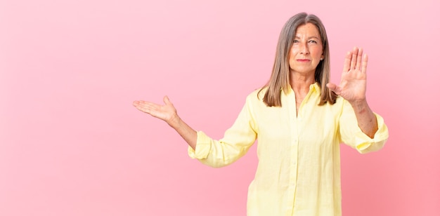 真剣に見えるかなり中年の女性が開いた手のひらを停止ジェスチャーを示しています