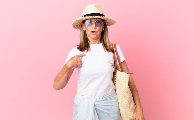 Довольно женщина среднего возраста выглядела шокированной и удивленной с широко открытым ртом, указывая на себя. летняя концепция
