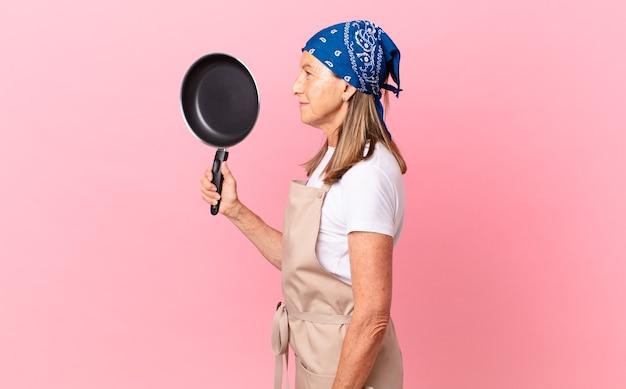 Довольно женщина среднего возраста на взгляде профиля думать, воображая или мечтать и держа сковороду. концепция шеф-повара