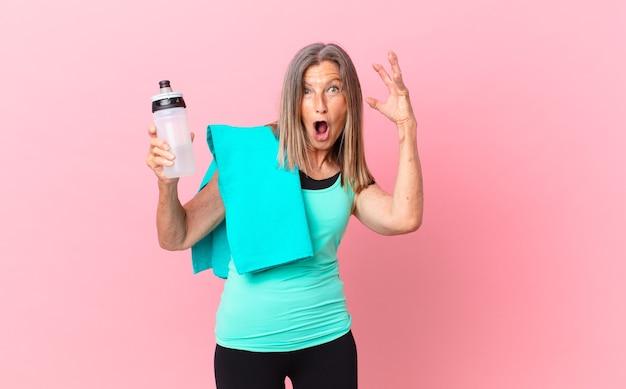 Довольно женщина среднего возраста кричала с поднятыми руками в воздухе. фитнес-концепция