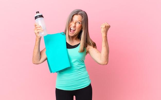 Довольно женщина среднего возраста агрессивно кричит с сердитым выражением лица. фитнес-концепция