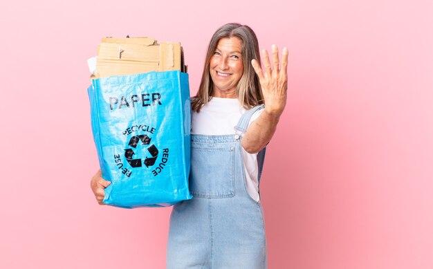 Довольно женщина среднего возраста улыбается и выглядит дружелюбно, показывая концепцию утилизации картона номер четыре