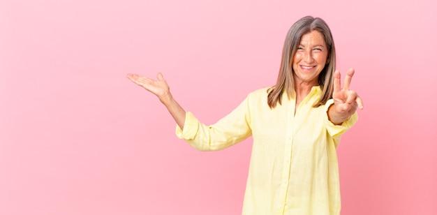 笑顔と幸せそうに見える、勝利または平和を身振りで示すかなり中年の女性