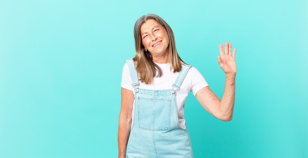 Pretty middle age woman smiling happily, waving hand, welcoming and greeting you