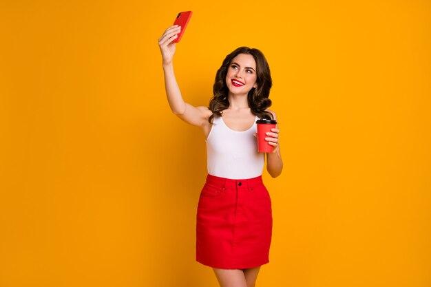 Симпатичная миллениальная дама держит кружку кофе по телефону и делает селфи в блоге