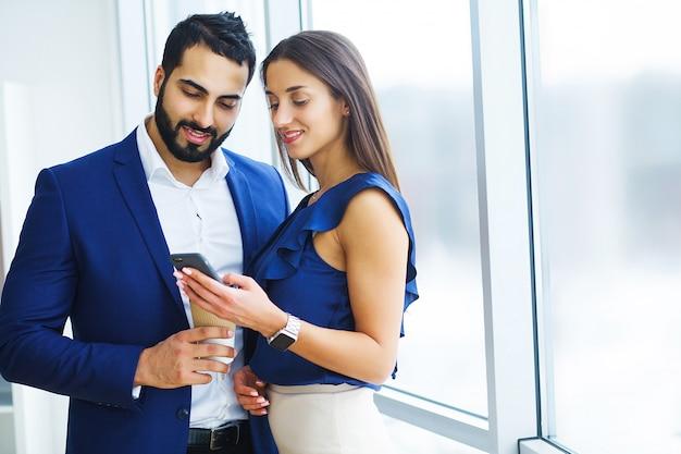 Женщина довольно смешанной расы и ее бородатый коллега по телефону обсуждают совместный проект в офисной компании
