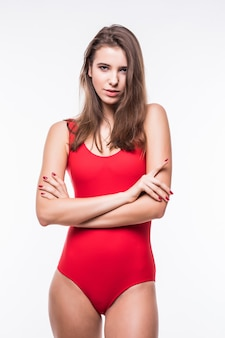 Pretty model girl in swimming suite holds arms on her belt isolated on white background