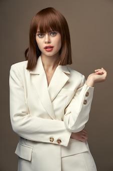 베이지 색 재킷에 예쁜 모델은 손으로 고립 된 공간으로 몸짓