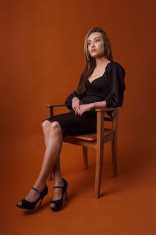 검은 드레스를 입은 예쁜 모델, 하이힐 신발은 주황색 배경의 의자에 앉아 있다