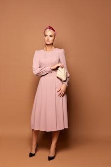 예쁜 모델 아가씨는 베이지 색 배경에 고립 된 긴 소매와 귀여운 분홍색 드레스를 입습니다.