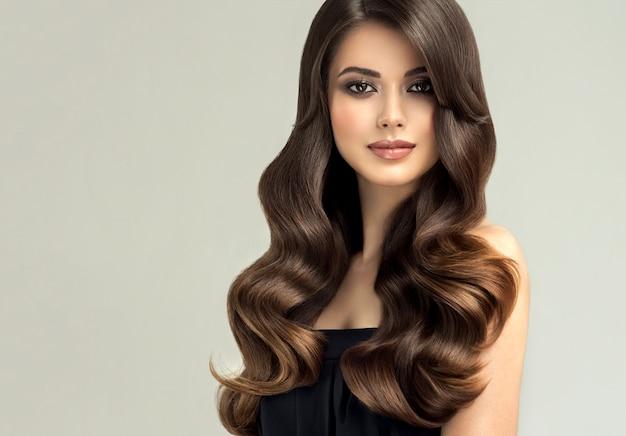 長い巻き毛の手入れの行き届いた髪のきれいなモデル優れた髪の波理髪アートとヘアケア